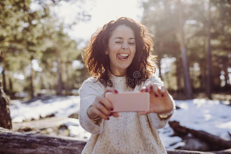 Giovane bella donna che si siede sui tronchi di legno e che prende un'immagine con il telefono cellulare Indicatore luminoso post immagini stock