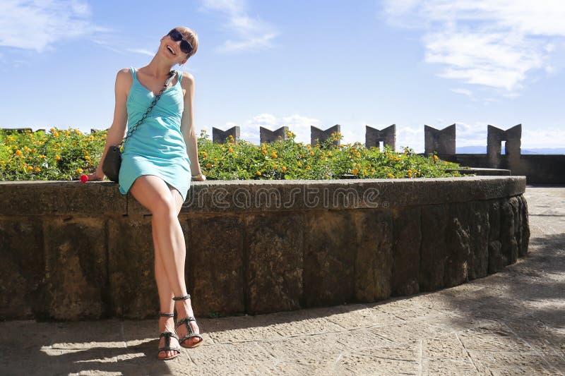 Giovane bella donna che si siede sull'aiola di pietra e sul sorridere Ragazza in breve vestito sexy da estate Felice turistico fe immagini stock