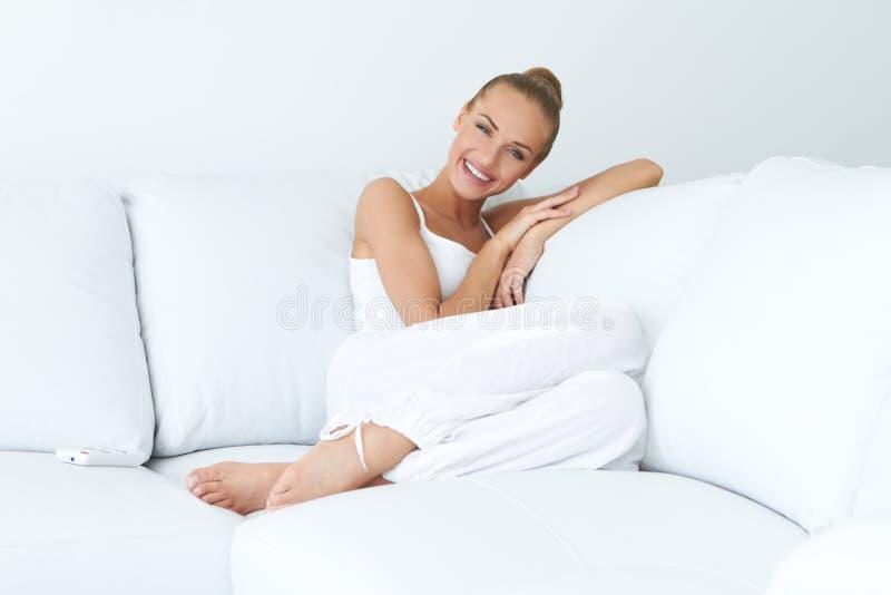 Giovane bella donna che si siede sullo strato fotografie stock libere da diritti