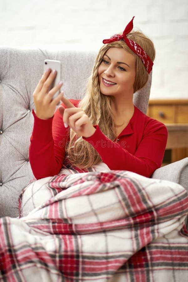 Giovane bella donna che si siede in una poltrona con un telefono avvolto in una coperta durante il tempo di Natale fotografie stock libere da diritti