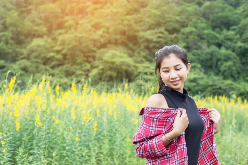 Giovane bella donna che sta nel godimento del giacimento di fiore fotografie stock libere da diritti