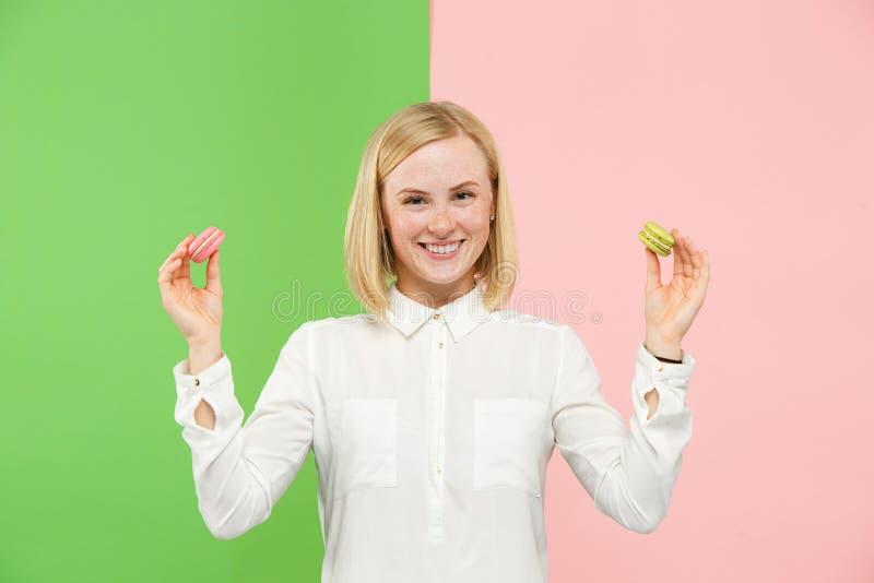Giovane bella donna che tiene la pasticceria dei maccheroni in sue mani immagini stock libere da diritti