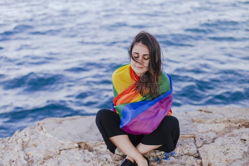 Giovane bella donna che tiene una bandiera gay dell'arcobaleno all'aperto STILE DI VITA un concetto di orgoglio L'amore ? amore immagini stock libere da diritti
