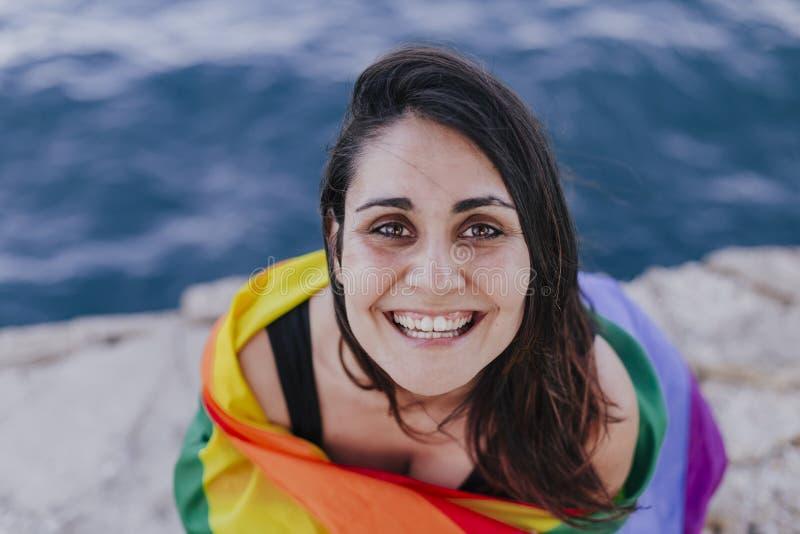Giovane bella donna che tiene una bandiera gay dell'arcobaleno all'aperto STILE DI VITA un concetto di orgoglio L'amore ? amore immagine stock