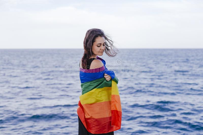 Giovane bella donna che tiene una bandiera gay dell'arcobaleno all'aperto STILE DI VITA un concetto di orgoglio L'amore ? amore fotografie stock