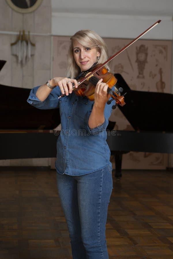 Giovane bella donna con capelli biondi ondulati che giocano viola, tenendo arco che sorvola strumento sulla sua spalla e che sorr fotografia stock libera da diritti