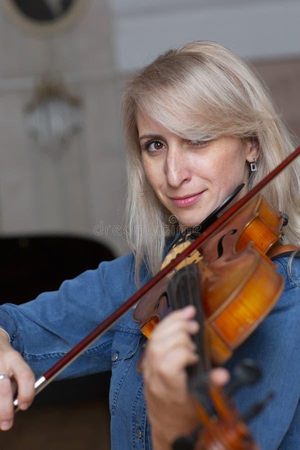 Giovane bella donna con capelli biondi ondulati che giocano viola, tenendo arco che sorvola strumento sulla sua spalla e che sorr immagini stock libere da diritti