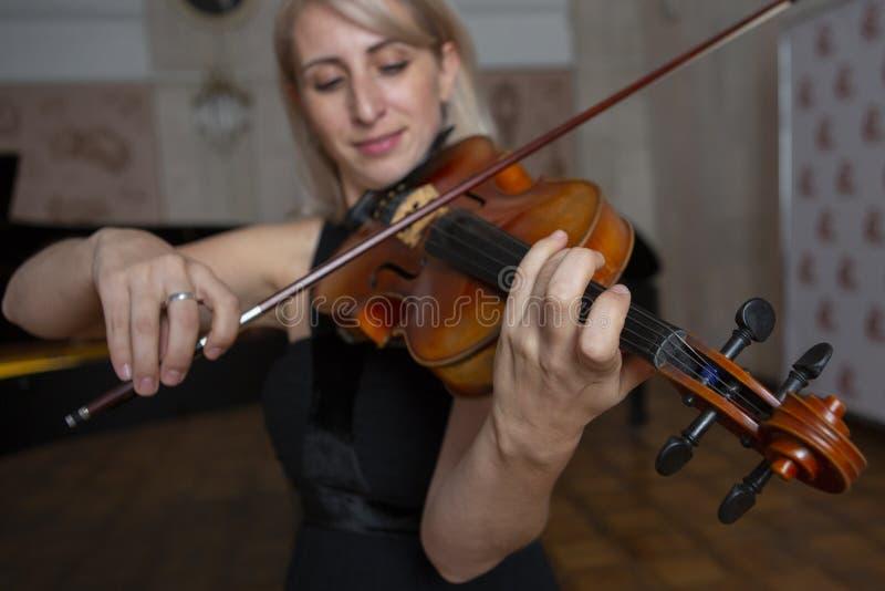 Giovane bella donna con capelli biondi ondulati che giocano viola, tenendo arco che sorvola strumento sulla sua spalla e che sorr immagini stock