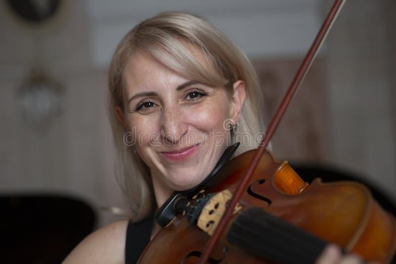 Giovane bella donna con capelli biondi ondulati che giocano viola, tenendo arco che sorvola strumento sulla sua spalla e che sorr fotografia stock
