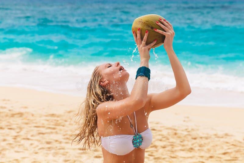 Giovane bella donna con capelli lunghi in bikini bianco, c bevente fotografia stock libera da diritti
