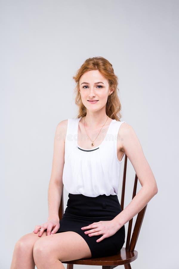 Giovane bella donna con capelli rossi e ricci lunghi che si siedono su una sedia di legno su un fondo bianco nello studio Vestito immagine stock libera da diritti