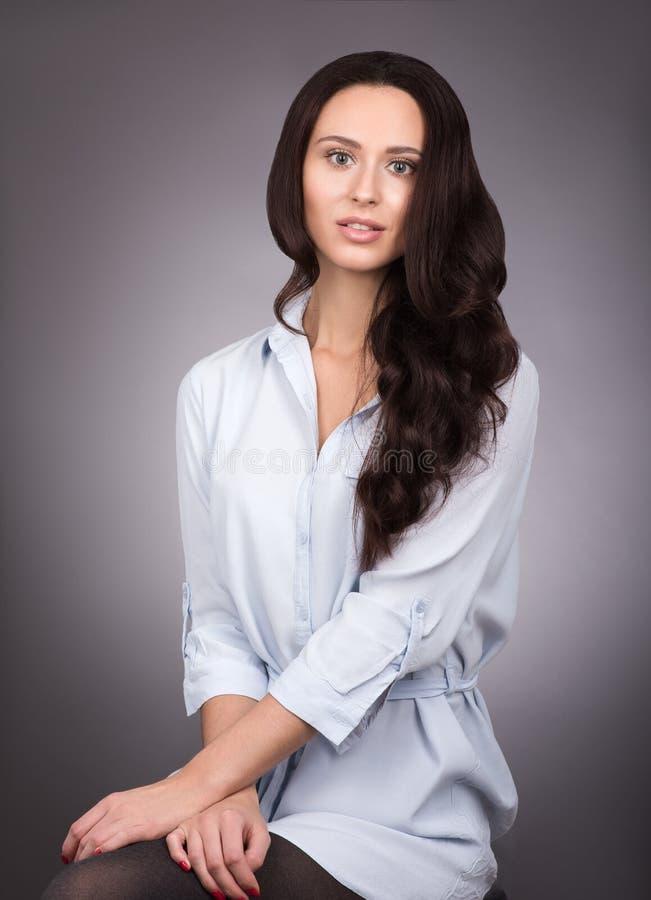 Giovane bella donna con capelli scuri lunghi e la camicia blu che posano su grigio immagine stock