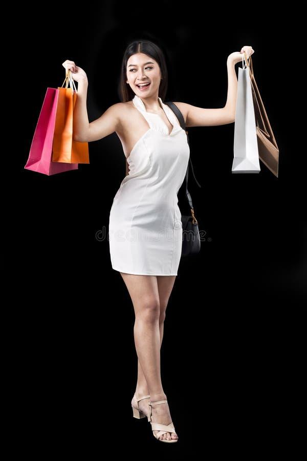 Giovane bella donna con i sacchetti della spesa che gode nell'acquisto immagini stock