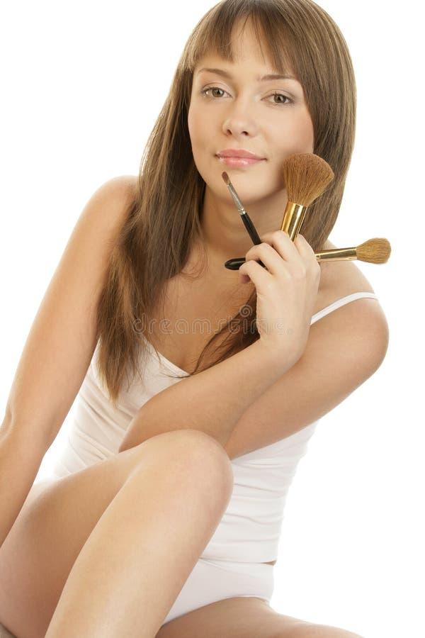 Giovane bella donna con il brushe naturale di trucco della tenuta di trucco fotografie stock
