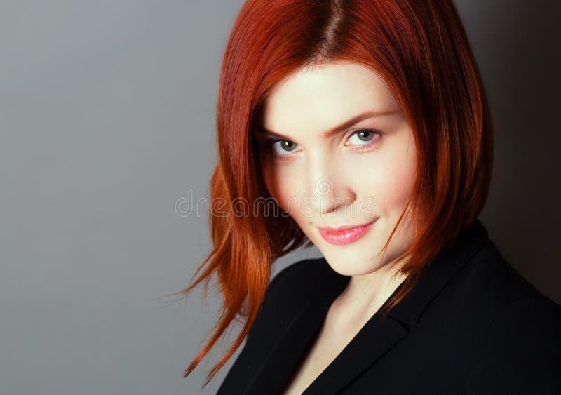 Giovane bella donna con il ritratto rosso di sorriso e dei capelli su fondo grigio scuro fotografia stock