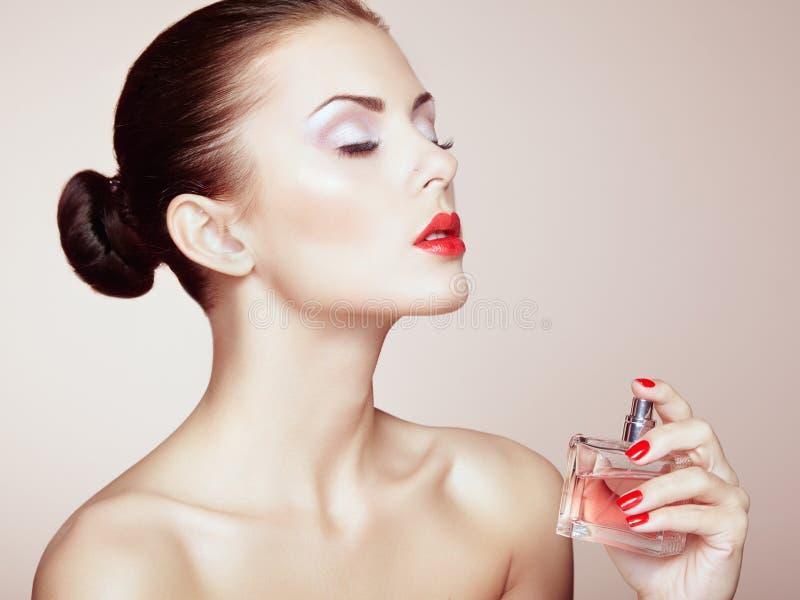Giovane bella donna con la bottiglia di profumo. Trucco perfetto immagini stock