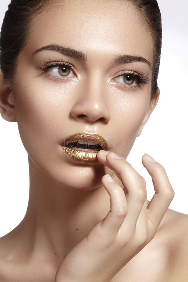 Giovane bella donna con pelle molle pulita, trucco luminoso delle labbra dell'oro Forme perfette delle sopracciglia Trucco di gio immagine stock