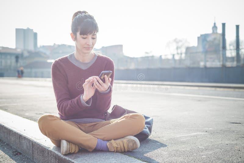 Giovane bella donna dei pantaloni a vita bassa che per mezzo dello Smart Phone immagine stock