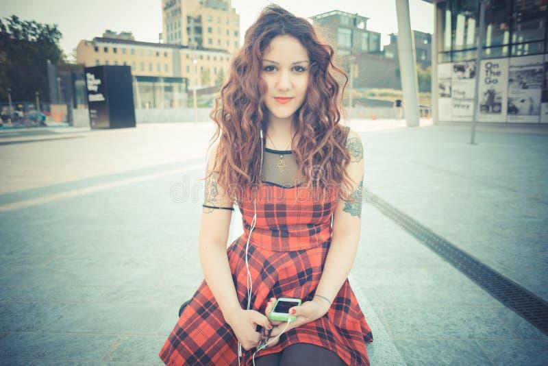 Giovane bella donna dei pantaloni a vita bassa con capelli ricci rossi immagine stock