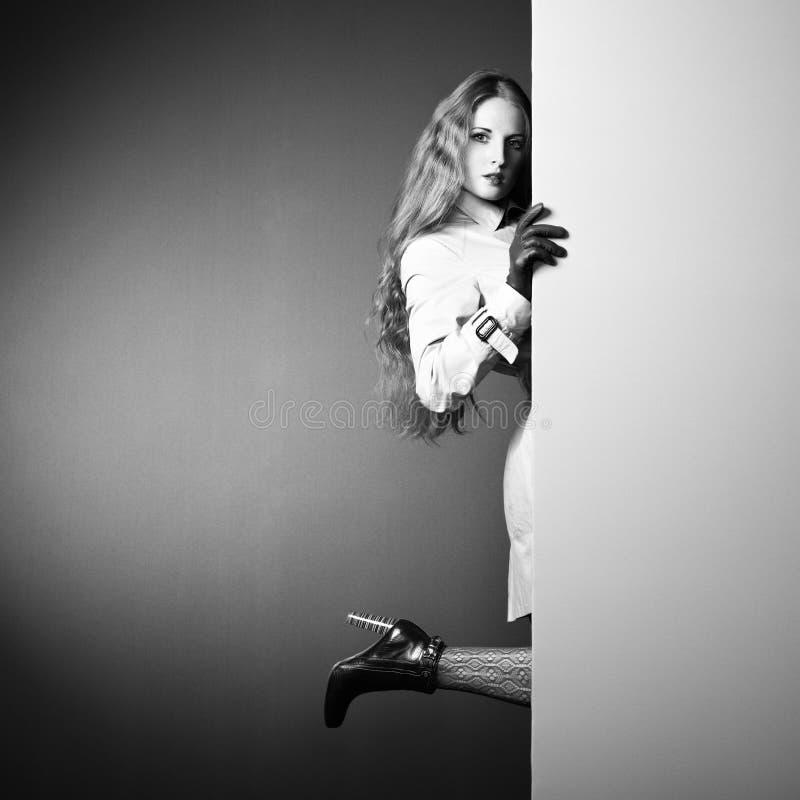 Giovane bella donna della foto in un impermeabile nell'interno fotografie stock libere da diritti