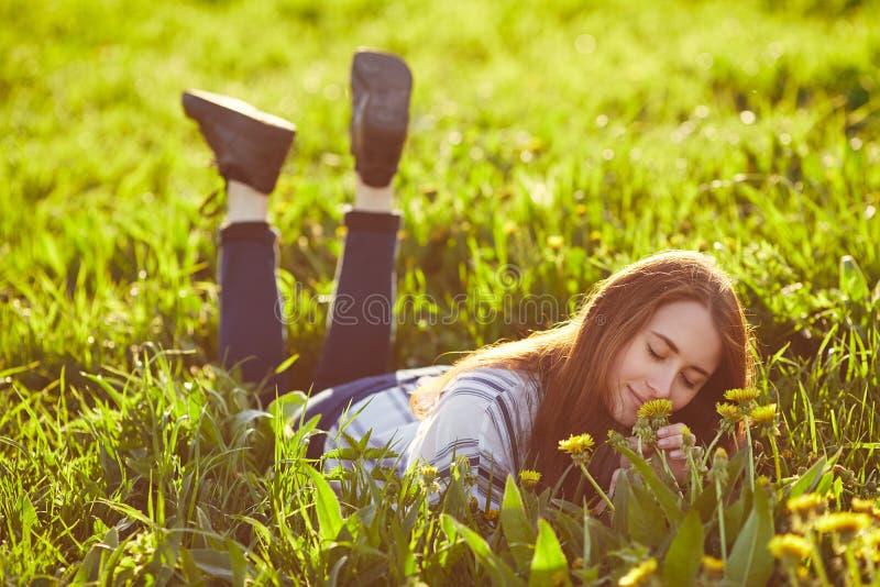 Giovane bella donna della testarossa che gode dell'odore del dente di leone di fioritura un giorno soleggiato Chiuda gli occhi immagine stock