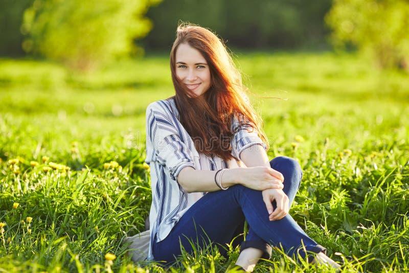 Giovane bella donna della testarossa che gode dell'odore del dente di leone di fioritura un giorno soleggiato Chiuda gli occhi fotografia stock libera da diritti