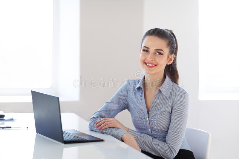 Giovane bella donna di affari con il computer portatile nell'ufficio fotografia stock