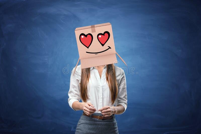 Giovane bella donna di affari con la scatola di cartone sulla sua testa immagine stock libera da diritti