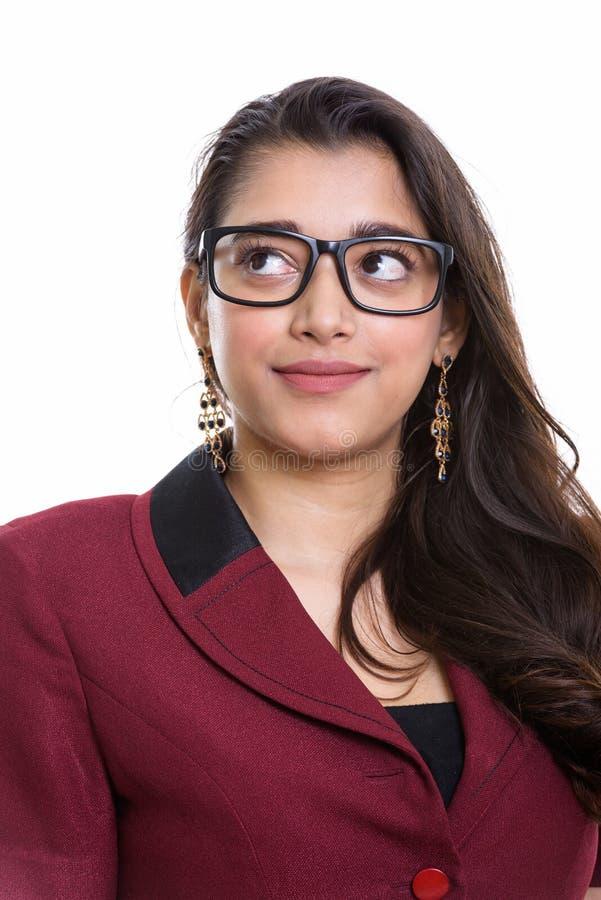 Giovane bella donna di affari indiana che pensa mentre cercando fotografia stock