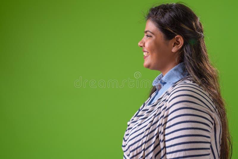 Giovane bella donna di affari indiana di peso eccessivo contro fondo verde immagini stock libere da diritti