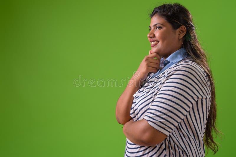 Giovane bella donna di affari indiana di peso eccessivo contro fondo verde immagine stock libera da diritti