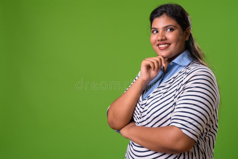 Giovane bella donna di affari indiana di peso eccessivo contro fondo verde fotografia stock libera da diritti
