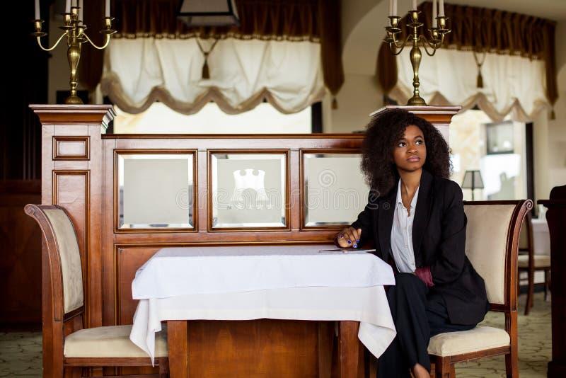Giovane bella donna di affari nera che si siede dalla tavola con la compressa in sue mani Vestito d'uso della donna fotografie stock