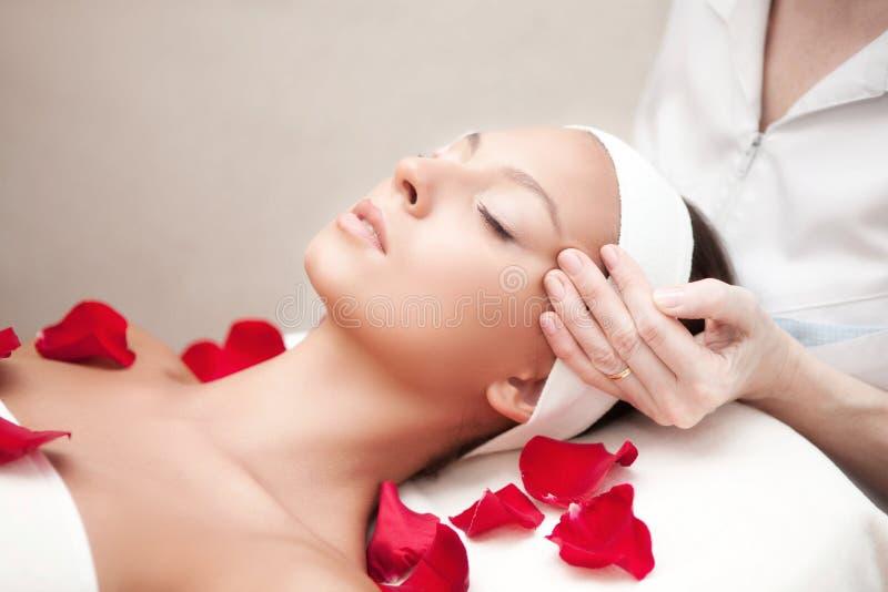 Giovane bella donna di rilassamento che ha un massaggio facciale immagini stock