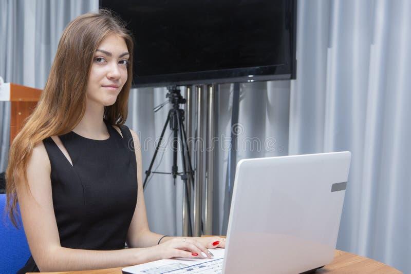 Giovane bella donna felice che per mezzo del computer portatile, all'interno fotografie stock libere da diritti