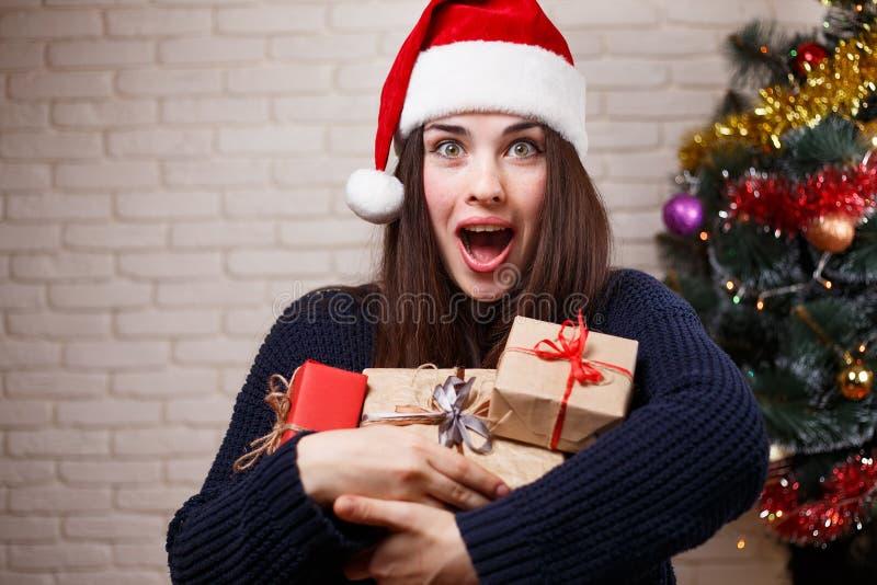 Giovane bella donna felice stupita in cappuccio di Santa con i molti regalo b immagini stock libere da diritti