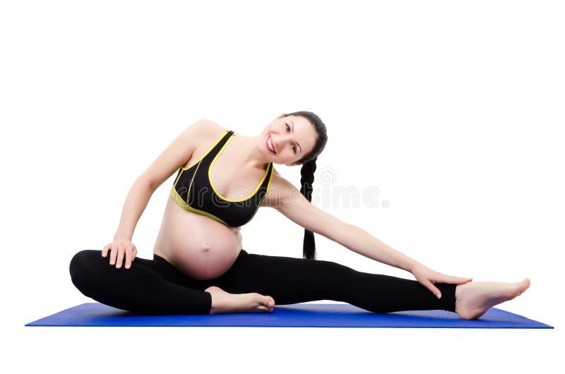 Giovane bella donna incinta che fa gli esercizi fotografia stock