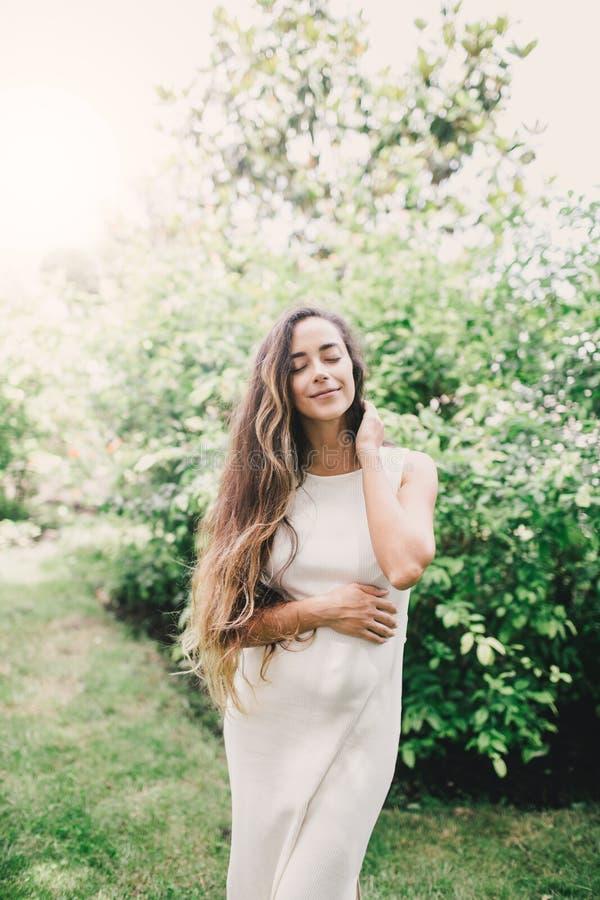 Giovane bella donna incinta con capelli ricci sani lunghi che posano in un parco verde fotografia stock