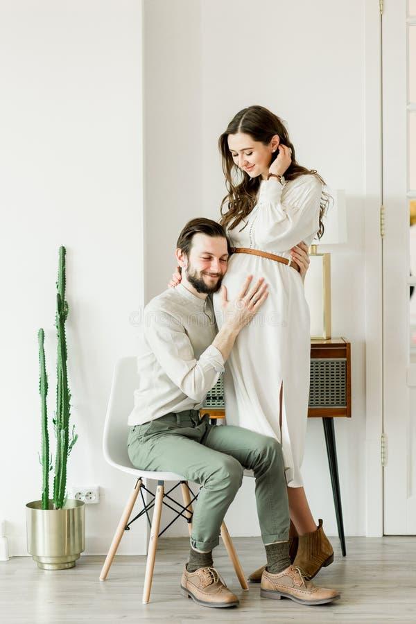 Giovane bella donna incinta ed il suo marito nella condizione del cappello vicino alla parete del cactus fotografie stock libere da diritti