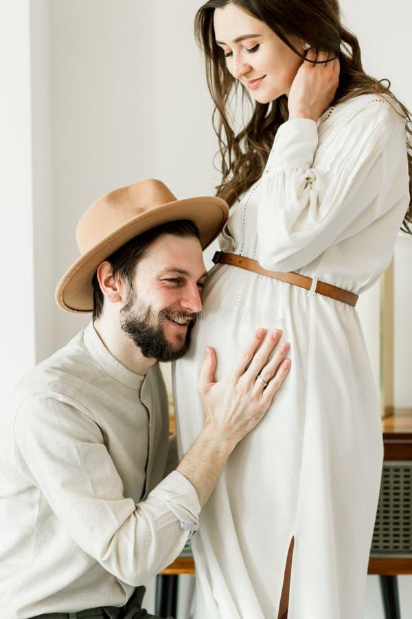 Giovane bella donna incinta ed il suo marito nella condizione del cappello vicino alla parete del cactus fotografia stock