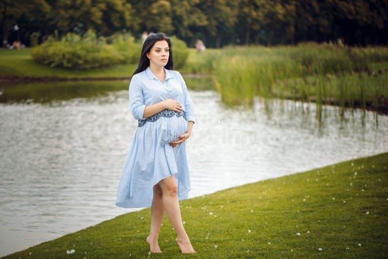 Giovane bella donna incinta felice in vestito blu che tocca la sua pancia con amore e cura vicino all'acqua nel parco fotografia stock