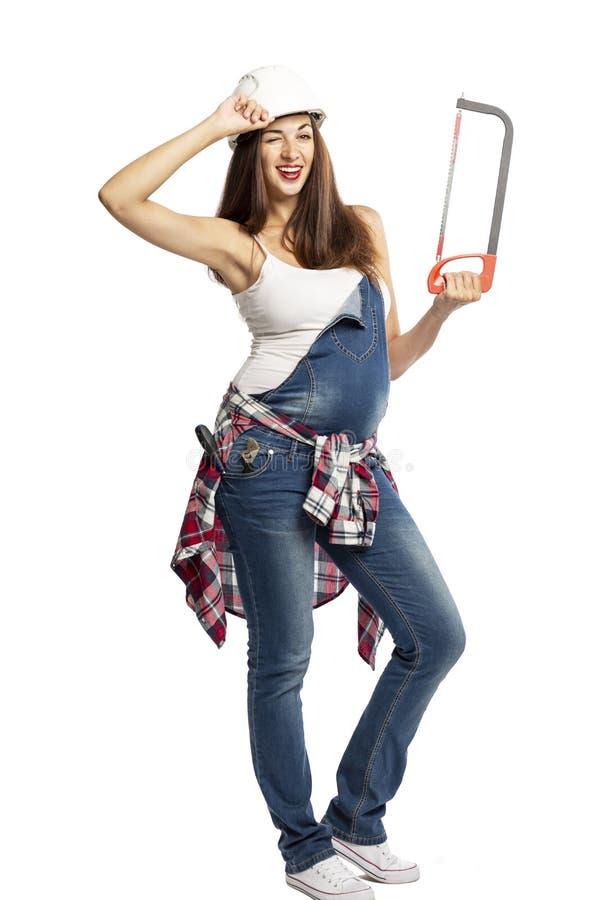 Giovane bella donna incinta in jeans e nel sorridere del casco della costruzione Nelle mani di uno strumento della costruzione fotografia stock