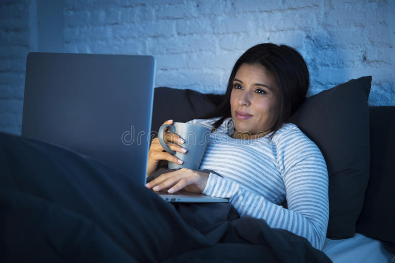 Giovane bella donna ispanica sul lavoro del letto a casa felice sul computer portatile alla notte immagini stock