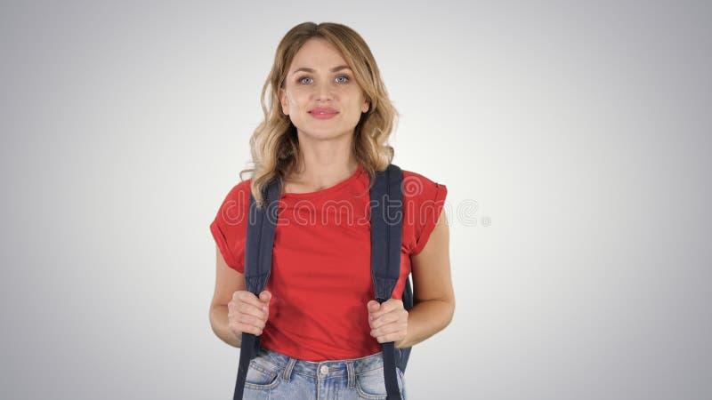 Giovane bella donna in maglietta casuale con lo zaino ed i jeans che cammina sul fondo di pendenza immagini stock libere da diritti