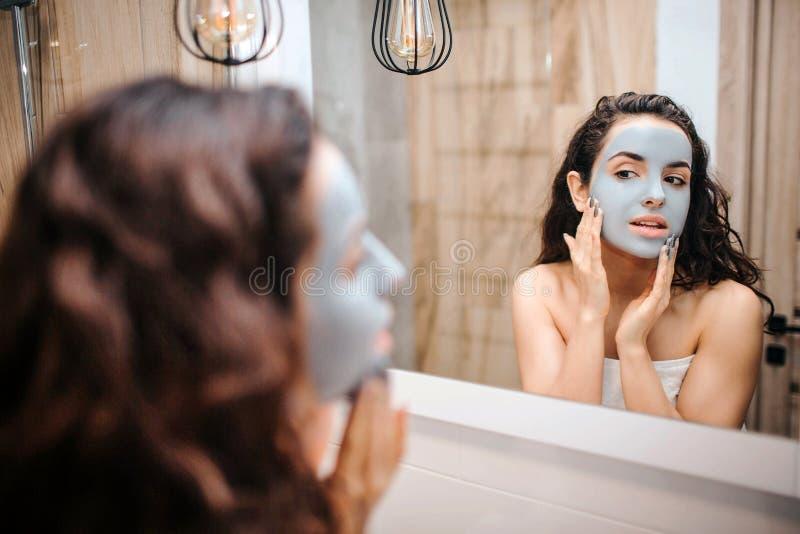 Giovane bella donna mora sportiva che fa routine di sera di mattina allo specchio Ha maschera crema sul fronte e sul tocco immagini stock