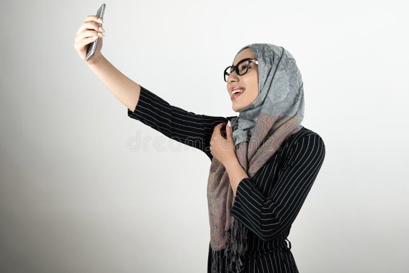 Giovane bella donna musulmana sorridente in vetri che indossano il hijab del turbante, smartphone della tenuta del foulard che sp immagine stock