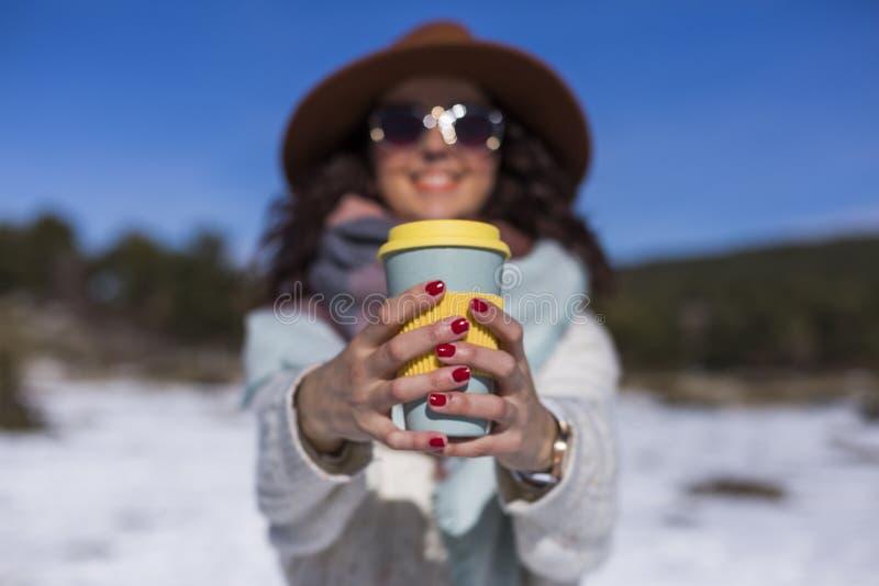 Giovane bella donna nella neve che tiene una tazza di tè o caffè e sorridere Ritratto di aria aperta, stile di vita immagine stock