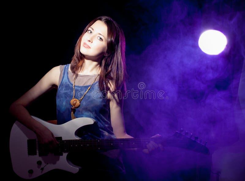 Giovane bella donna in scena con una chitarra. Nebbia sopra immagine stock
