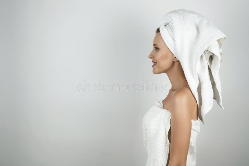 Giovane bella donna sorridente in asciugamano bianco sopra il corpo e sulla sua testa che sta fondo bianco isolato di profilo fotografie stock