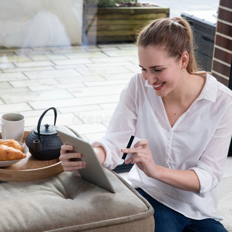 Giovane bella donna sorridente che gode del commercio elettronico dalla compressa domestica fotografie stock